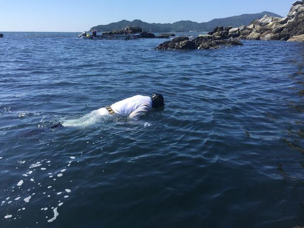 海に浮く白装束の男性