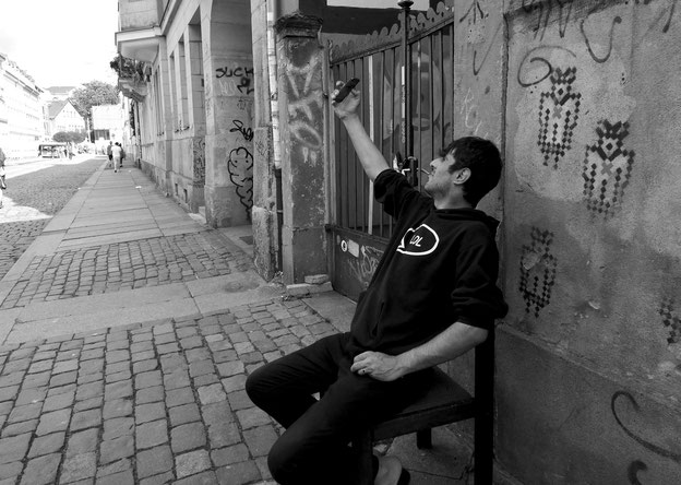 Fotografie von Elena Pagel, zeigt einen Mann der auf der Straße auf einem Stuhl Sitzt und ein selfie von sich macht.
