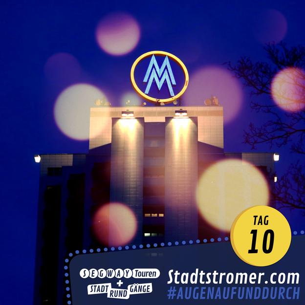 Wintergartenhochhaus in Leipzig bei Nacht mit beleuchtetem Doppel-M