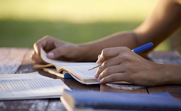 Frauenhände mit Stift und Notizbuch