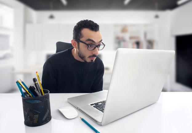 Mann mit Brille, der entsetzt in seinen Laptop schaut