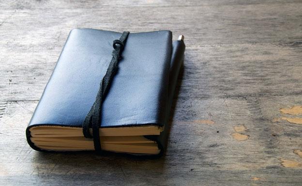 Schwarzes Tagbuch auf einem Holztisch