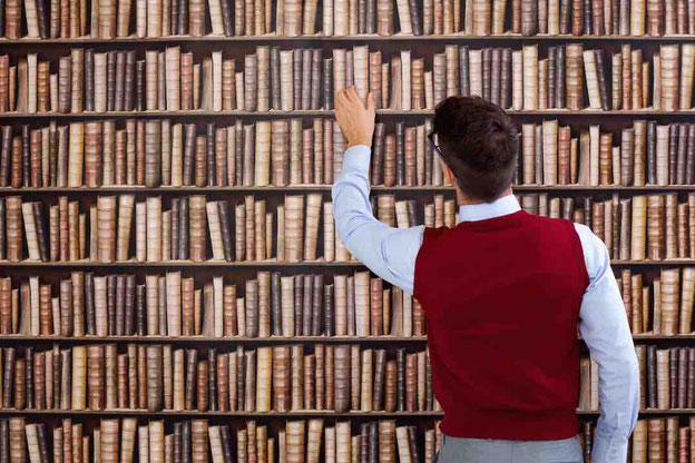 Mann vor Bücherregal – Studium