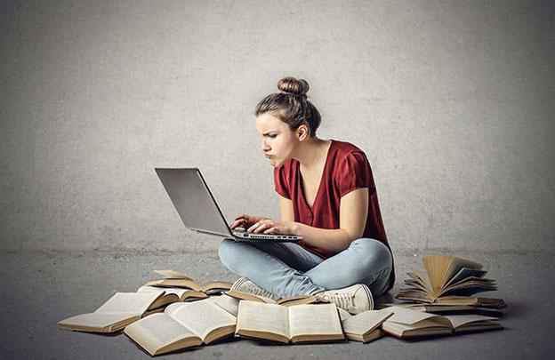 Mädchen, das am Boden sitzt und am Laptop schreibt