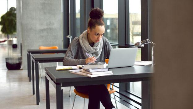 Studentin am Schreibtisch mit Laptop und Büchern