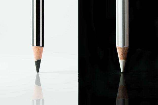 Ein schwarzer und ein weißer Stift als Symbol für das Lektorat und das Korrektorat