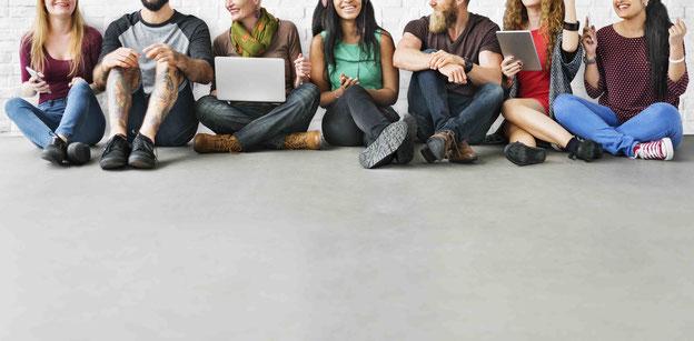 Eine Gruppe von Personen sitzt am Boden und plaudert gemütlich