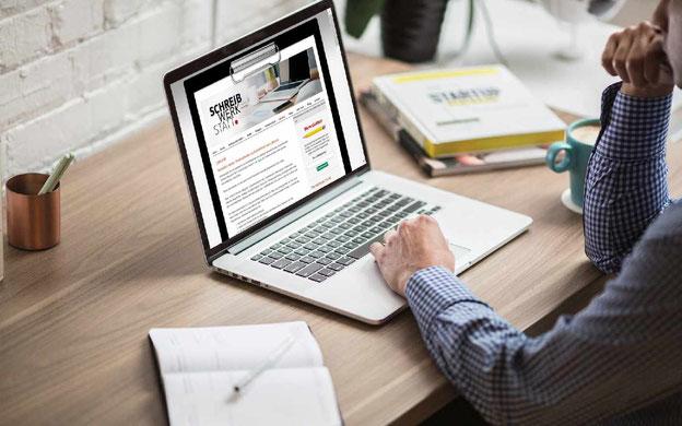 Mann vor einem Laptop sitzend