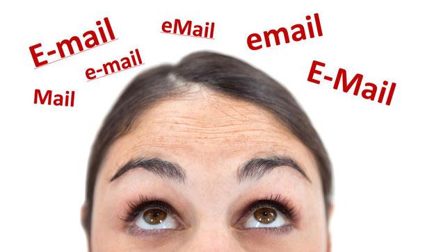 """Frau, die nach oben zu den unterschiedlichen Schreibweisen von """"E-Mail"""" schaut"""