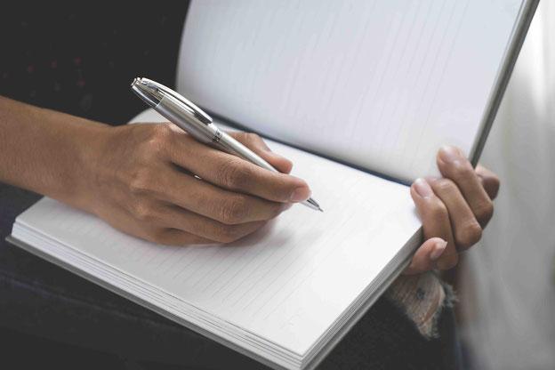 Offener Schreibblock auf dem Schoß einer Frau