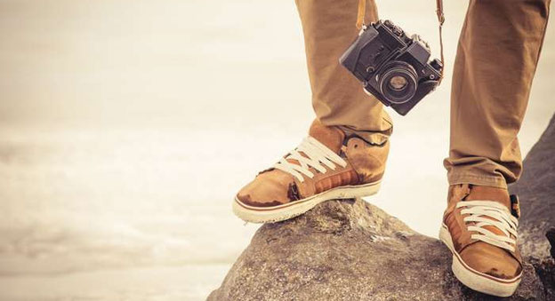 Füße eines Mannes, der auf einen Felsen steht, und Kamera