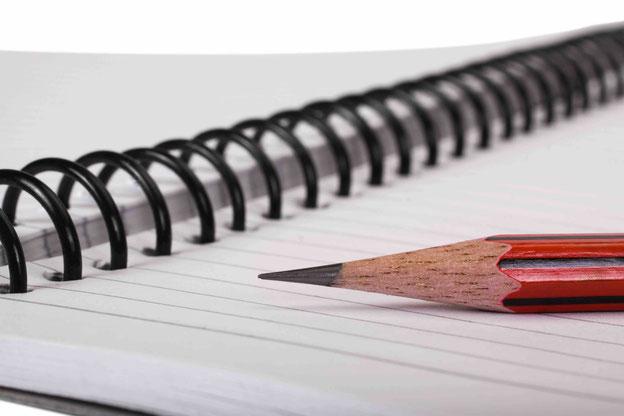 Gespitzter Bleistift auf liniertem Schreibblock