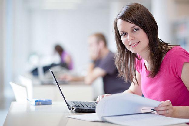 Student mit Laptop auf Treppe sitzend