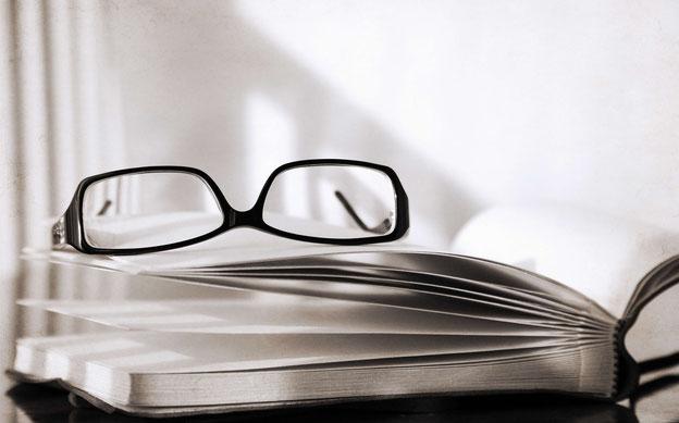 Geöffnetes Buch, auf dem eine Brille liegt
