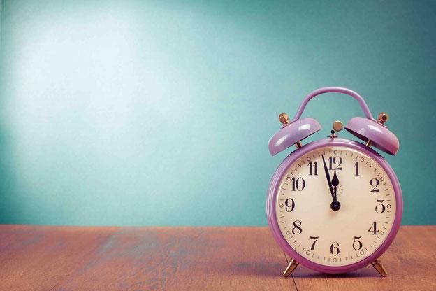Eine Uhr zeigt kurz vor 12 Uhr an