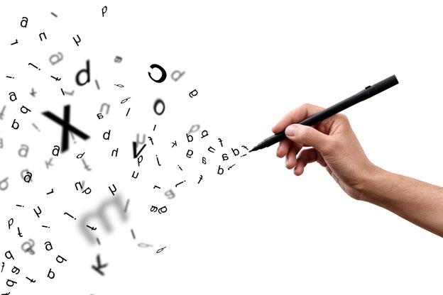 Schreibende Hand mit Stift und Buchstaben