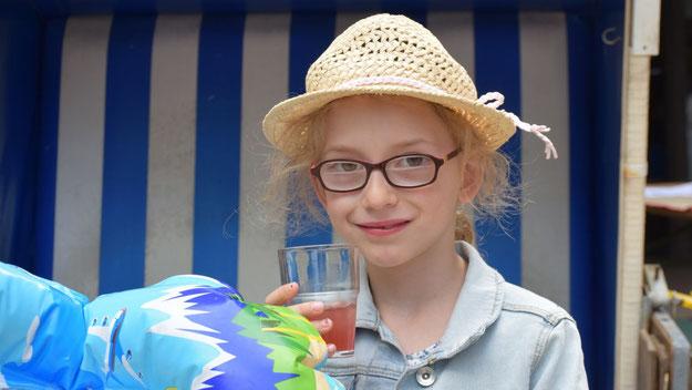 Stilgerecht mit Strohhut: Eine kleine Besucherin genoss einen fruchtigen Drink.