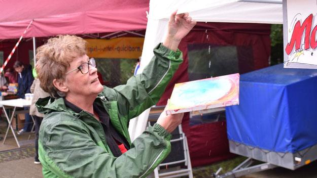 Wird das jetzt Kunst? Die Quickborner Malerin Frauke Klinkforth an ihrem eingeregneten Stand.