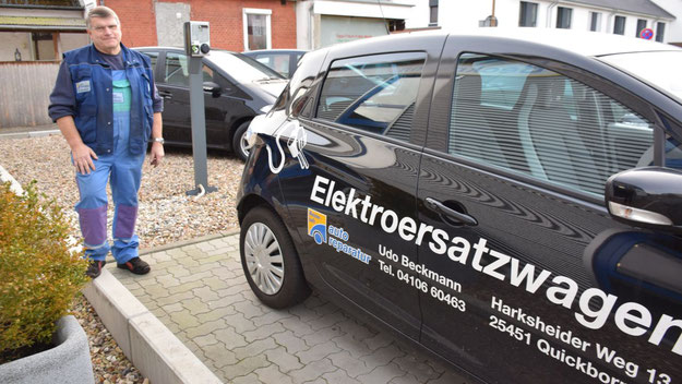 Meister Udo Beckmann mit der Ladestation und seinem Elektroersatzwagen.