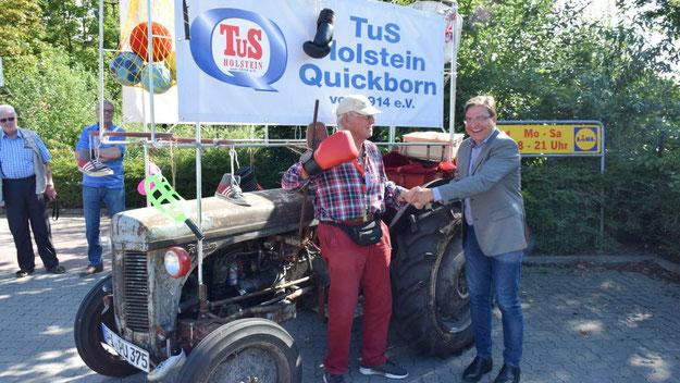 Einen uralten Ferguson-Trecker mit Benzin-Motor  hatte Peter Schneider (85) flott gemacht, um damit  für den TuS Holstein Quickborn mitzufahren. Bürgermeister Köppl freute sich mit