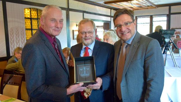 Bürgervorsteher Henning Meyn (M.) überreichte gemeinsam mit Bürgermeister Köppl dem Ausgezeichneten ein gläsernes Quickborn-Wappen