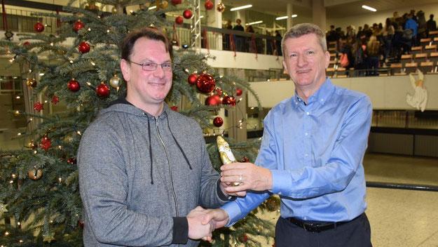 Als Dank für das Engagement überreichte Schulleiter Dr. Brandt dem Projektleiter Matthias Junge stellvertretend für das gesamte Team einen Schokolanden-Weihnachtsmann und weitere Süßigkeiten