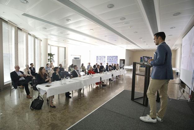Raum mit Powerpointpräsentation und Rednerpult auf der rechten Seite. Davor sitzend die Jury