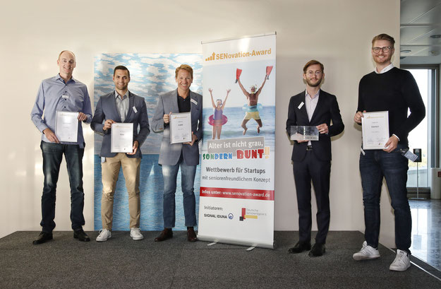 Fünf Personen stehen mit Urkunden neben dem SENovation Award Roll up