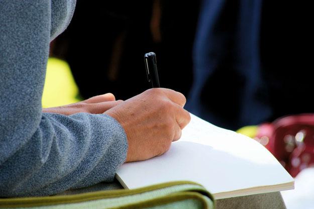 Hände mit Stift und einem Tagebuch