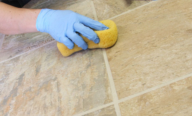 A man with a sponge cleaning grout joints