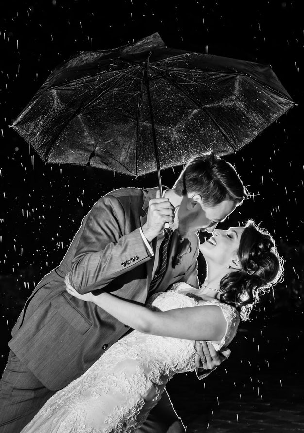 Black and white photo of bride and groom dancing in the rain. Groom is holding umbrella. Rain is backlit.