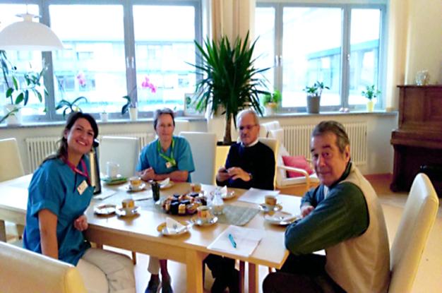 """Die Palliativ-Schwestern Paula Suchy und Katrin Licht, Dr. Zeuner und Herr Alois Marx (von li.) im """"Wohnzimmer"""" bei Kaffee und Kuchen. Das fotografierte Schw. Heike."""