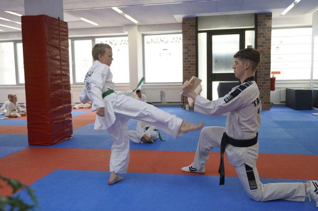 Eine Junge während einer Gürtelprüfung der Kindergruppe im Taekwondo tritt gegen ein Brett.