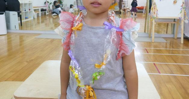幼稚園児がつくったキャンディレイを首にかけて出来上がりを確認。上手にできてとてもうれしそうです。