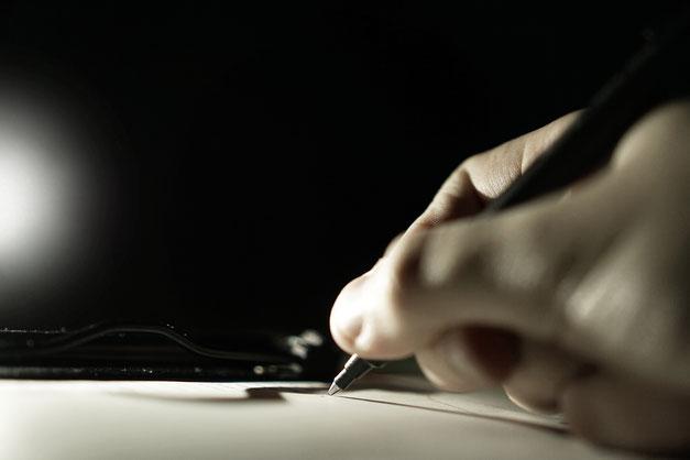 Person schreibt auf Papier