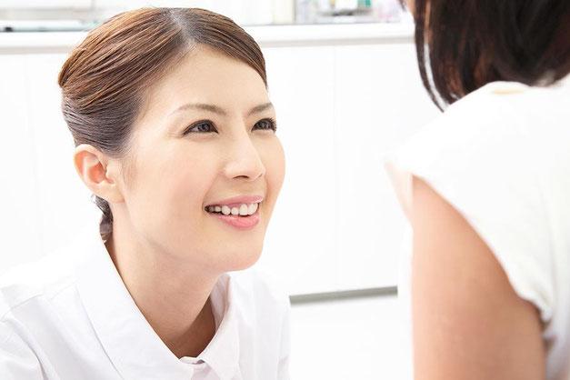 患者の顔を笑顔で見上げるやさしそうな笑顔の看護師