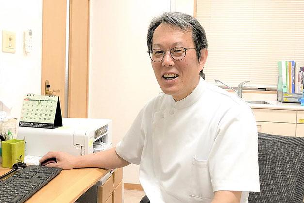 診察室のデスクで笑顔のきたばやし医院 院長