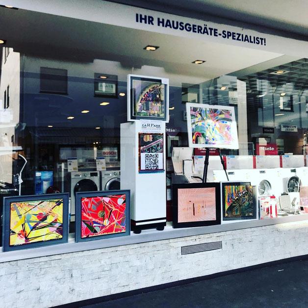 Schaufenster der Firma Elektro Mantel in Nidda mit der Präsentation von sechs der Arbeiten von Andreas Alka. Foto vom Künstler,  QR-Code für Künstler Homepage sowie der Hinweis zur parallel laufenden Ausstellung im Autohaus Carpark in Nidda.