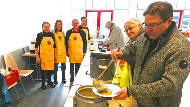 Bürgermeister Köppl stärkt sich an der vom Lions-Club betreuten Essensausgabe mit einem Teller Erbsensuppe