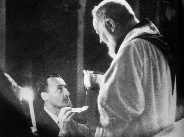 Luigi Peroni riceve la comunione da Padre Pio