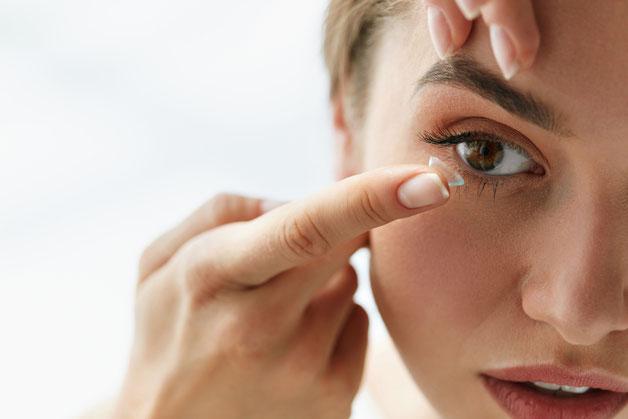 Patientin beim Einsetzversuch einer Kontaktlinse