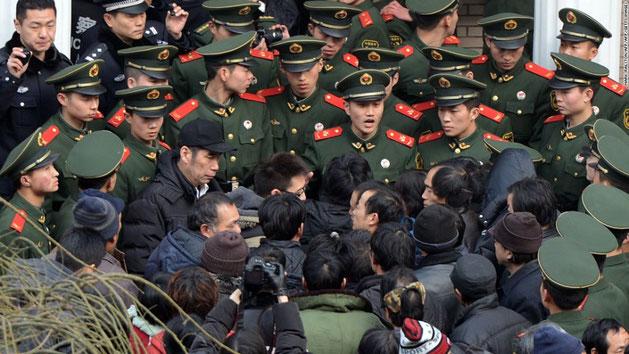 Migrantarbejdere demonstrerer for bedre lønforhold i Bejing og bliver standset af politistyrker.