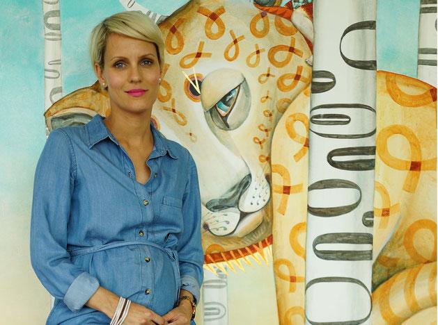 Schwangere in Jeanskleid vor Gemälde
