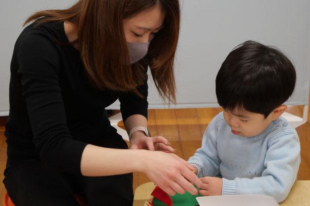 幼児教室1歳児の親子で学ぶステッラコースで、モンテッソーリの活動をしているお子様を、お母さまが見守っています。