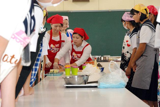 サンドイッチの作り方を教える山崎製パンの鈴木さん(右)と上保さん