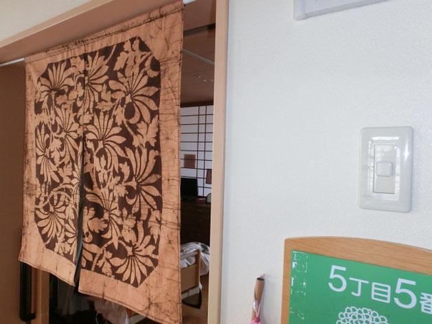 歴史を重ねた風呂敷で作った、ご家族お手製ののれんが居室にマッチング