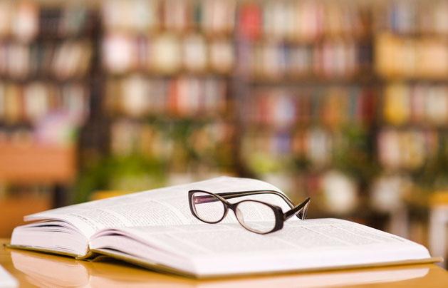 Aufgeschlagenes Buch mit Lesebrille vor Bücherregal