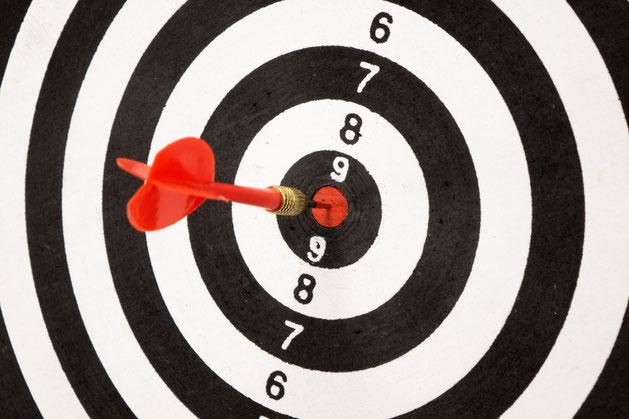 Zielscheibe mit rotem Dartpfeil in der Mitte