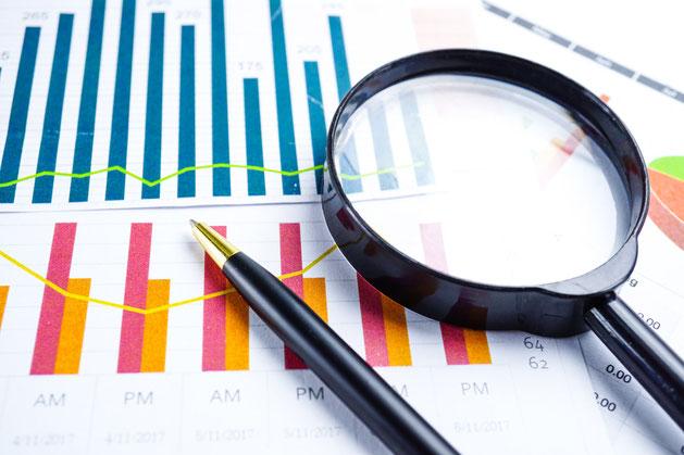 Statistiken mit Lupe und Stift