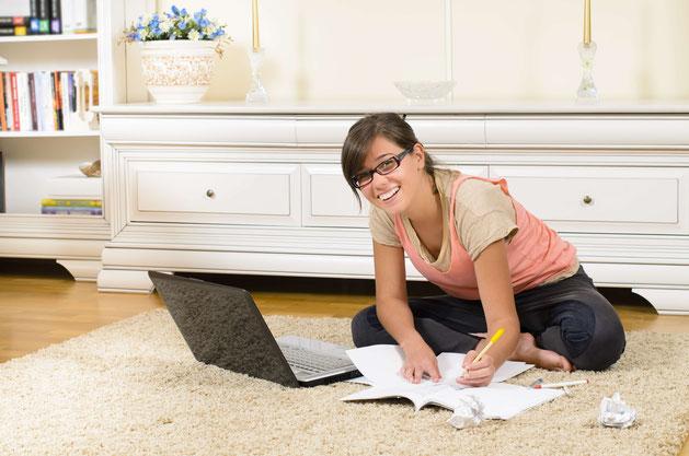 Studentin sitzt am Boden und schreibt